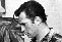 "Beat icon Jack Kerouac holds a paper scroll like those discovered in 2005 that included previously unknown works as well as the original manuscript for his most famous novel, ""On The Road."""