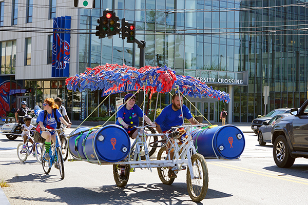 Rowdy River Rover team members Jacqui Gallant and John Fedirko peddle past University Crossing while Sarah Galevi trails on a bicycle during the Lowell Kinetic Sculpture Race.