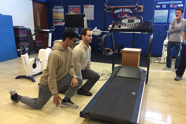 Lecturer Kyle Coffey, right, demonstrates an easy way to assess ankle mobility.