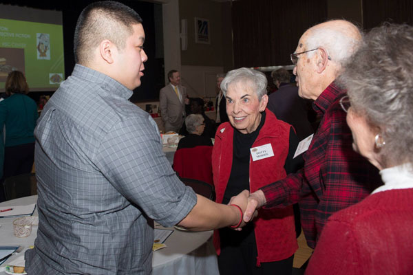 Scholarship recipient Renoel Amogawin chats with members of the Learning in Retirement Association after the awards ceremony at LIRA's annual holiday party.