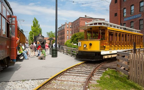 Park visitors wait as a yellow trolley tour arrives in Lowell