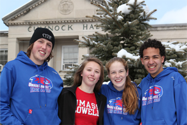 Four students in UMass Lowell sweatshirts in front of snowy Cumnock Hall