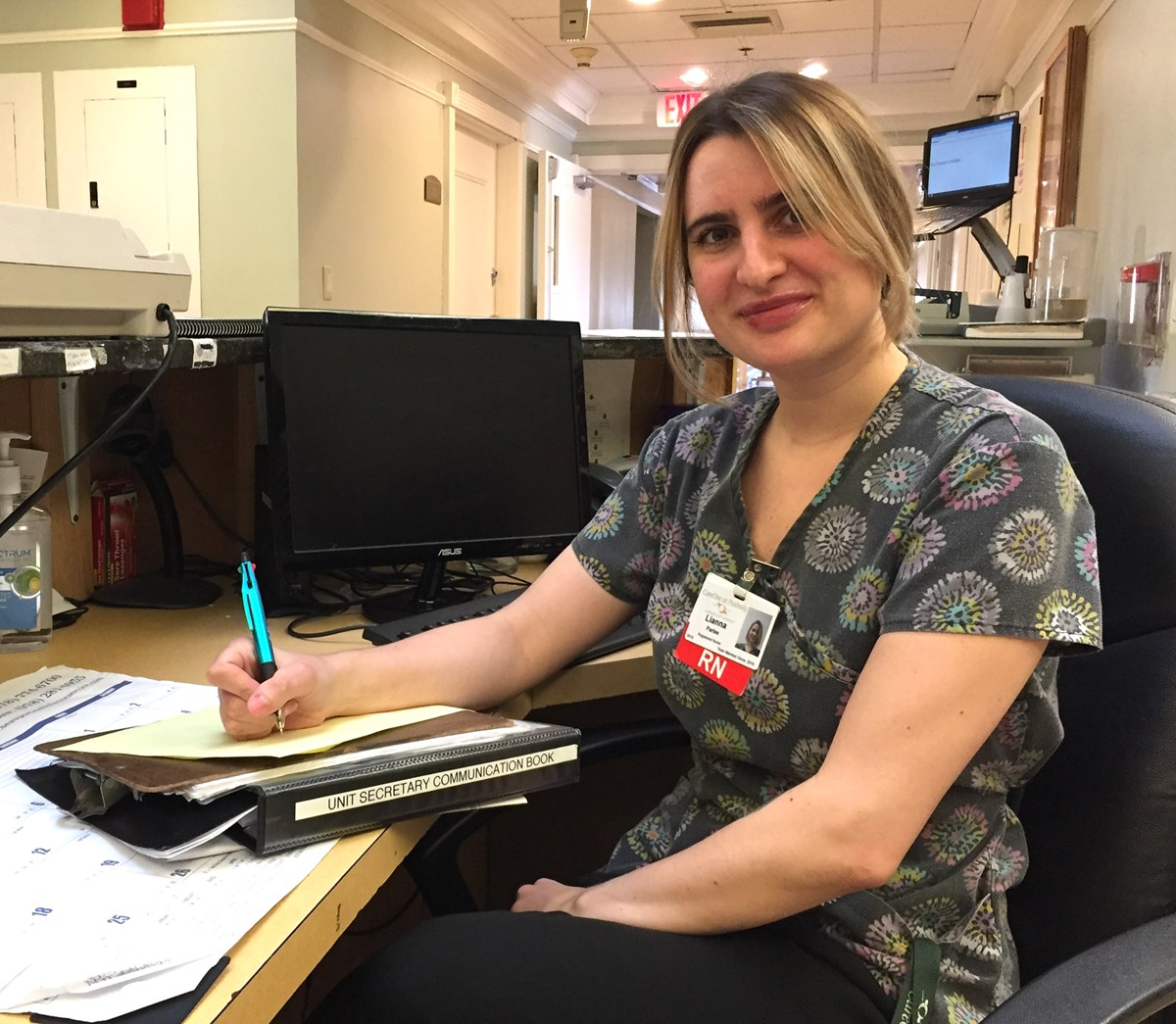 Lianna Partee taking notes at a desk working as an RN at a hospital