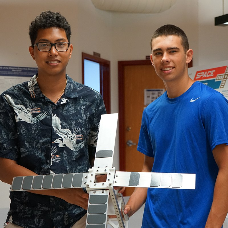 Liono and Matt, mechanical engineering students at the Lowell Center for Space Science and Technology with the CubeSat satellite