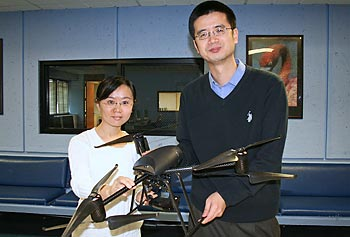 Computer Science Ph.D. student Zhongli Liu, left, and Asst. Prof. Xinwen Fu hold a prototype of the remotely operated 'HAWK' mini chopper.