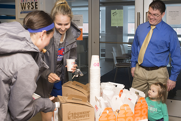 Faculty adviser David Adams and his daughter offer coffee and donuts to freshmen in the Honors College LLC.