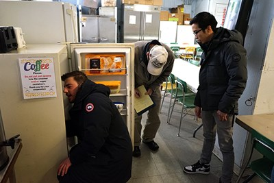 Orhan Kallogjeri inspects a refrigerator while Tu Anh Huynh looks on