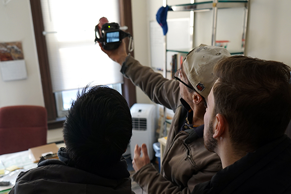 Barry Moyer shows Orhan Kallogjeri and Tu Anh Huynh how to use a thermal imaging camera to detect poorly insulated walls.
