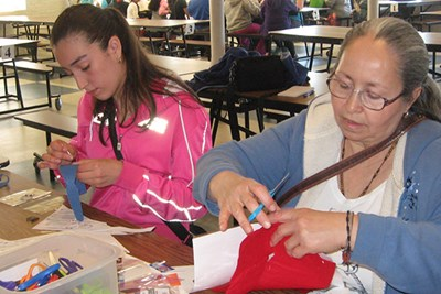 Students sewing circuit bracelets with steel thread at a LNHP class