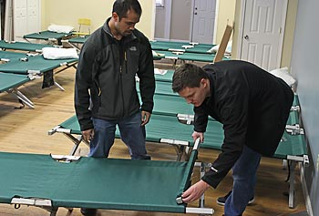 Undergraduate students Andrew Alpuerto, left, and Eric Blake assemble the redesigned cots at the Lowell Transitional Living Center.