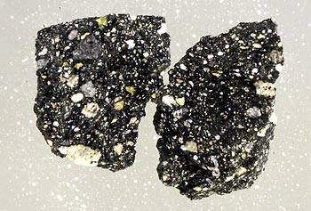 This close-up view of pieces of breccia from the Moon shows light-colored rock fragments and mineral grains embedded in a dark matrix. The 4-billion-year-old specimens each measure about 5 mm wide. They were part of a sample collected from the Moon's Taurus-Littrow valley by the Apollo 17 astronauts in 1972.