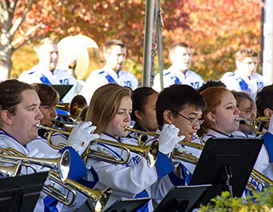 The Umass Lowell band group performing outside a field on Umass Lowell.