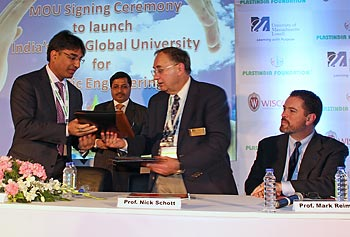 Plastics Engineering Prof. Emeritus Nick Schott, second from right, exchanges documents with Ashok Goel, president of Plastindia Foundation, during the signing ceremony in New Delhi, India. Looking on at right is Mark Reimer of UMass Lowell's Office of University Advancement.