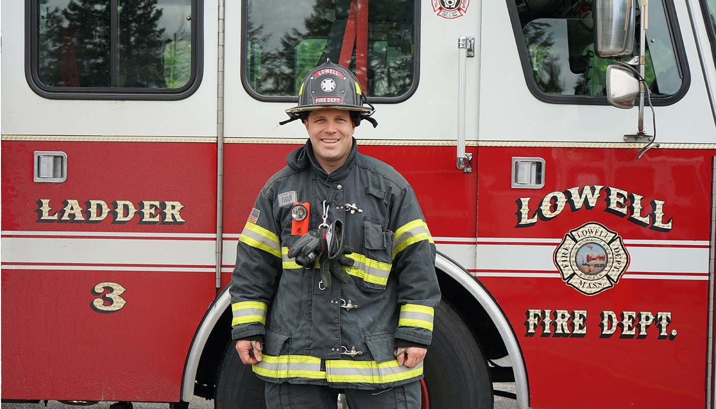 Lowell firefighter David Provencher in front of fire truck