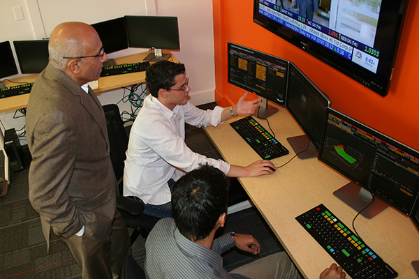 Finance Department chair Yash Puri watches juniors Alex Martinez, center, and Naveen Kumar try out the Bloomberg terminals in the Manning School's new Finance Lab and Trading Room.