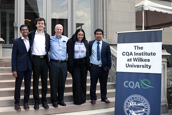 Alum Ed Keon, center, helped Manning School of Business finance students, from left, Bony Ganugapanta, Greg Montemurro, Katie Sanchez and Thavady Pech attend the CQA Institute's Advanced Investment Management course at Wilkes University in Wilkes-Barre, Pa.
