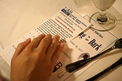 A student touches a Braille alphabet card