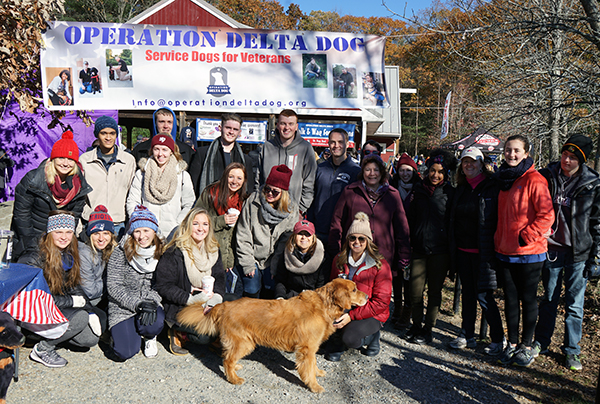 Students from the Manning Women in Business club pose with faculty advisor Elise Magnant's golden retriever, Guinness, at the Walk & Wag fundraising event in Carlisle.