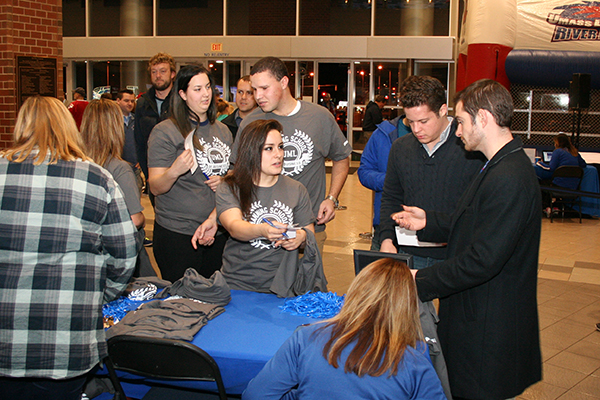 Honors marketing students sell Manning School T-shirts to alumni before a hockey game at the Tsongas Center.