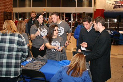 Honors marketing students sell Manning T-shirts at a hockey game