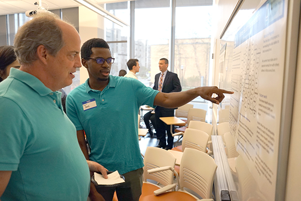An MSBA grad student explains his project to a guest at the capstone presentation ceremony