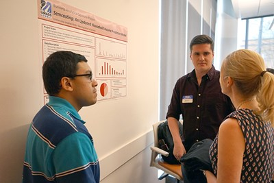 Students Jonathan Wolfe and Cristian Joia discuss their capstone project with a guest