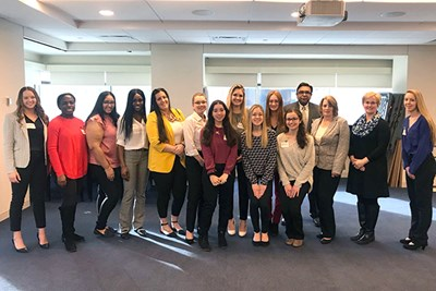 Business students pose with two alumnae working at Loomis Sayles