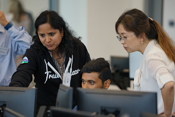 A Salesforce Student Ambassador, left, helps fellow students get started with Trailhead during a training session in the Pulichino Tong Business Center Trading Room.