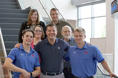 Ludwig Marek poses with two UML hockey players and four faculty and staff members