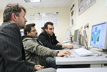 "From left, Prof. Martin Margala, Vikas Kaushal and Ignacio de la Torre from the Universidad de Salamanca in Spain working in the lab on the design of a ""ballistic deflection transistor."""