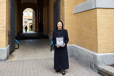 Marjorie Yang stands in front of Southwick Hall with the photo of her father