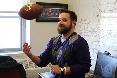 Asst. Prof. Spencer Ross tosses a football in his office