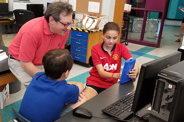Computer science Prof. Fred Martin teaches Medford middle school students Domenic Bruno and Maria Colombo how to create apps for mobile devices.