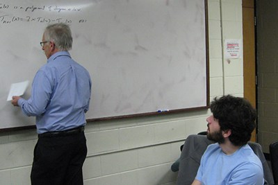 Prof. Ken Levasseur writes a problem on the board while math major Matthew D'Angelo looks on.