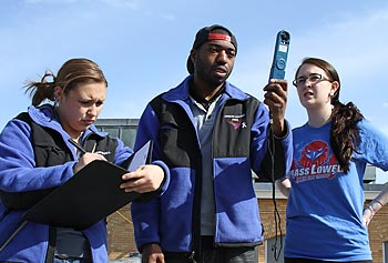 From left, meteorology sophomore Michaella Farese, senior Eli Policape and sophomore Corinne Clifford take weather measurements with their handheld instrument in preparation for the 117th Boston Marathon.
