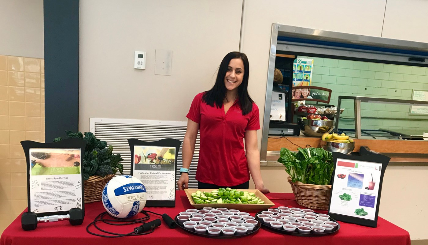 UMass Lowell alumni Michelle Palladino pictured in a school cafeteria with a table full of healthy snacks and information on leading a healthy lifestyle