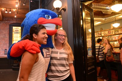 Two students pose with Rowdy the River Hawk at Mill No. 5