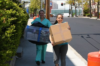 Katie Bilodeau and Zayna Basma carry donations to the House of Hope