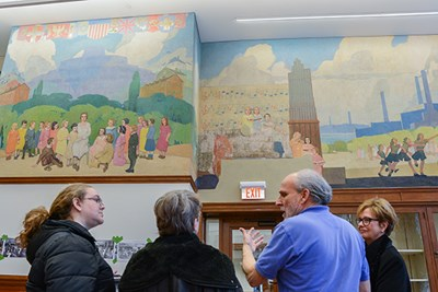Conservator Gianfranco Pocobene, second from right, discusses the Coburn Hall murals with Chancellor Jacquie Moloney, right, and others.