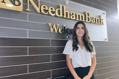 Nadine Chamoun standing in front of Needham Bank signage