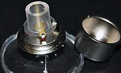 The nanocanary sensor uses a quartz crystal (thin disk mounted on the metal base) to detect changes in the health of cells living in a solution of nutrients above the crystal (clear cylinder attached to the quartz).