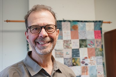 UMass Lowell College of Education Assoc. Prof. James Nehring in his office, with a quilty made by families of his former students