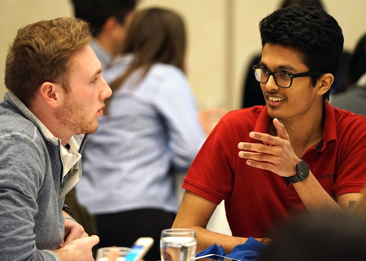 Nisarg Jhaveri speaks with another young man at a table