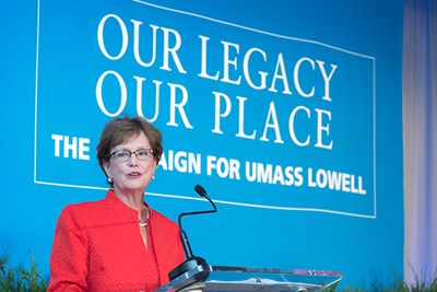 Chancellor Jacquie Moloney speaks in front of Our Legacy, Our Place banner