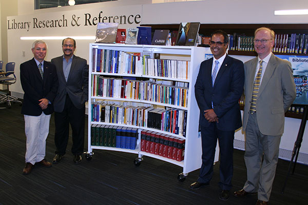 Celebrating the donation of more than 300 books to the UMass Lowell Library's Portuguese Collection are, from left, Prof. Frank Sousa, FAHSS Dean Luis Falcon, Regional Director of the Azorean Communities Paulo Teves and Libraries Director George Hart.