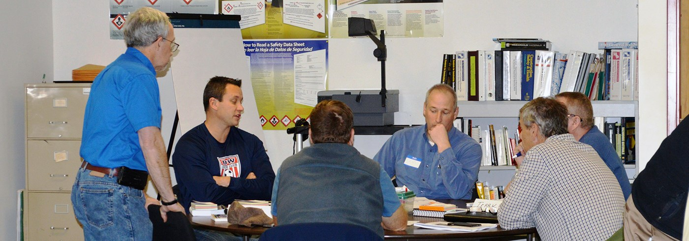TNEC trainer, Fred Malaby works with students at TNEC's training center at UMass Lowell. Fred works with a group of students gathered at a round table, discussing topics on health and safety in the construction industry.