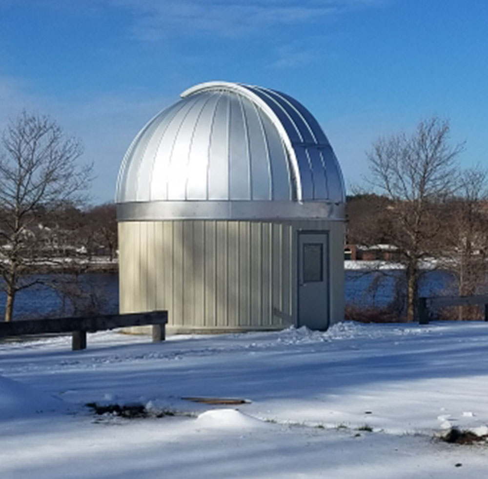 The dome has been added to the observatory. The observatory currently sits in a field of snow. The Merrimack River is visible in the background.