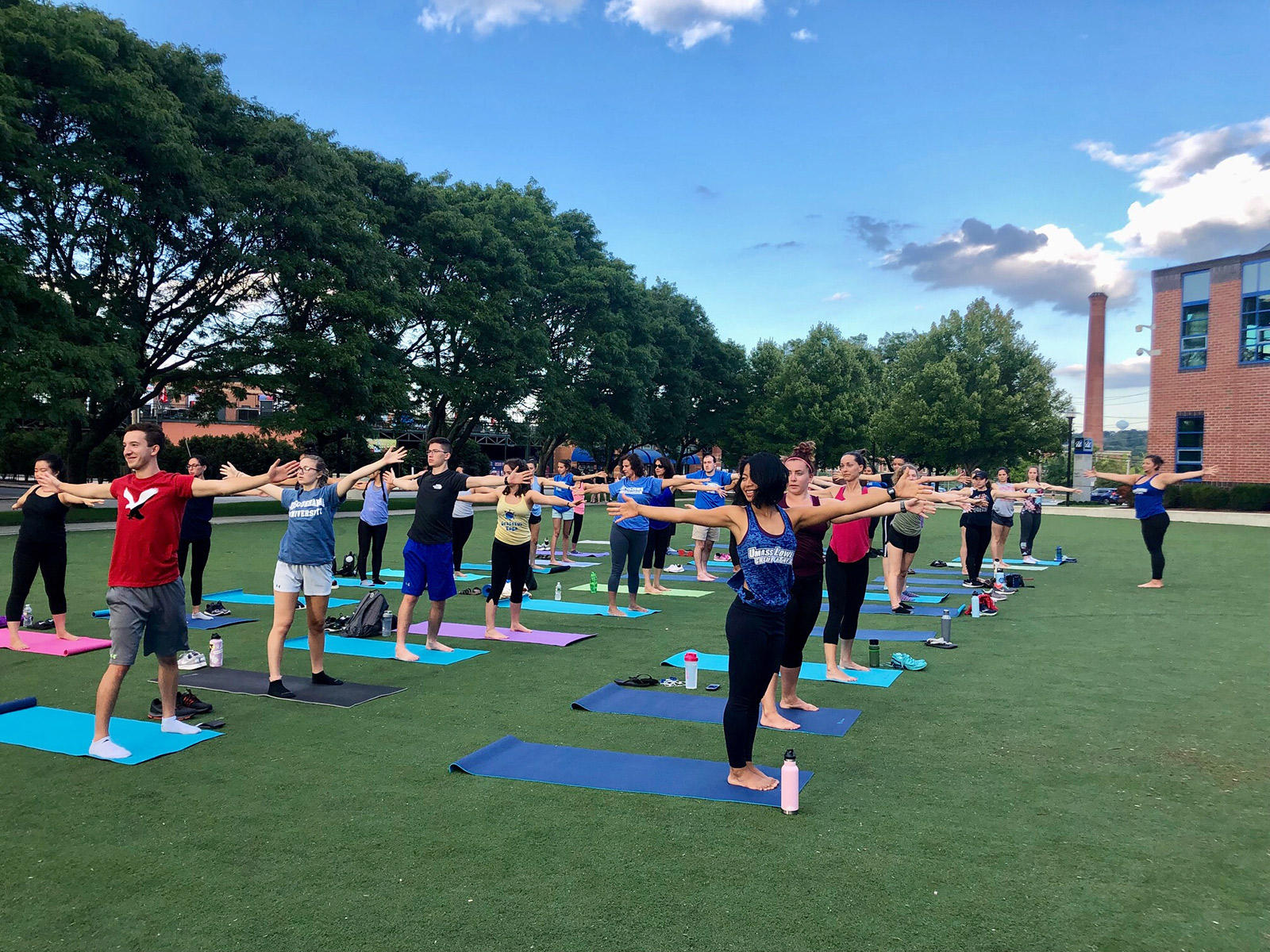 Yoga class in front of CRC on turf