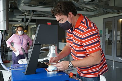 UML engineering technician Patrick Casey tests a mask for aerosol penetration at the Fabric Discovery Center