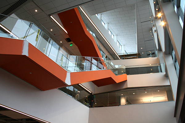 The Pulichino Tong Business Center's main staircase, as seen from the ground floor, adds a touch of orange to the open atrium.